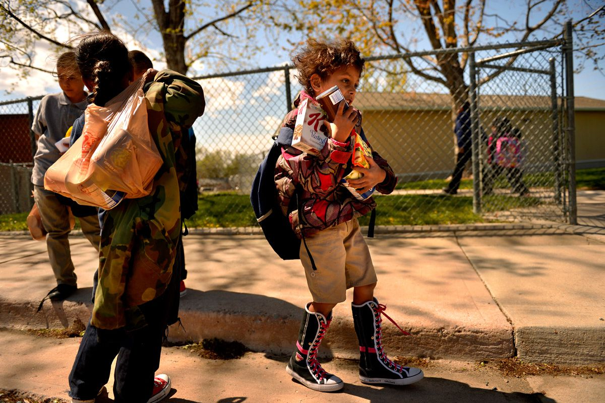 Homeless children in Aurora walk with bags of donated food after school.