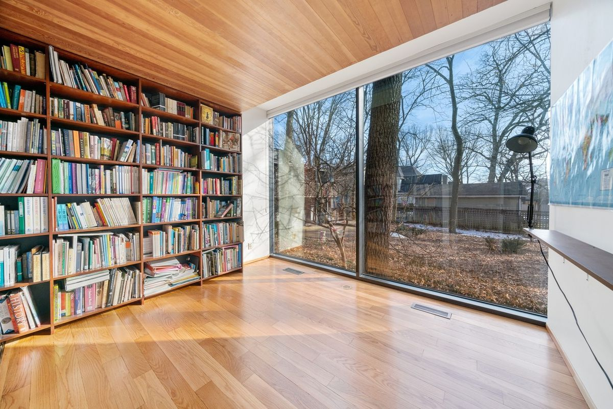 A wall of books next to a floor-to-ceiling glass wall overlooking a yard and trees.