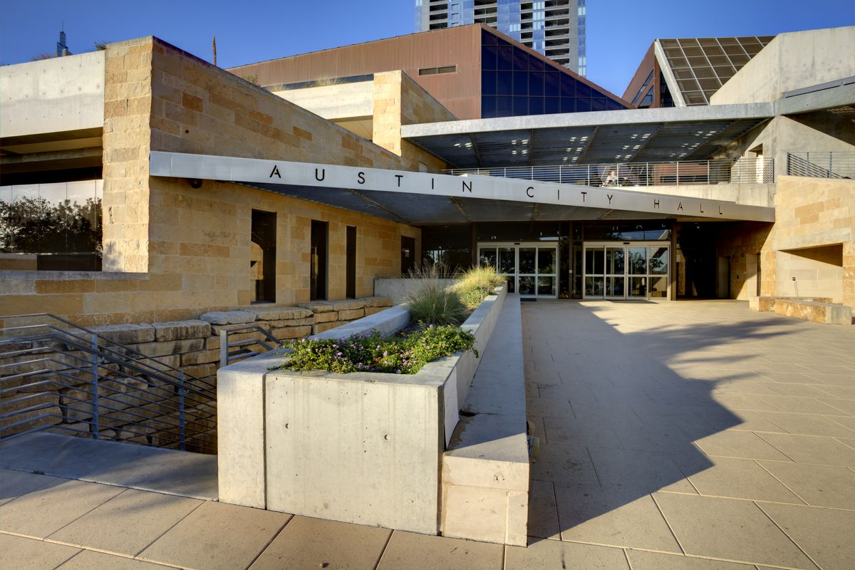 """A low-slung stone and metal civic building with signage reading """"Austin City Hall."""""""