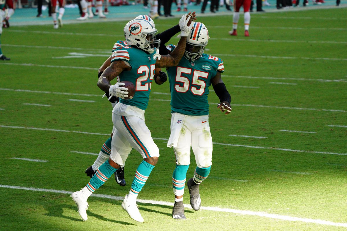 Xavien Howard #25, Nik Needham #40, and Jerome Baker #55 of the Miami Dolphins celebrate and interception against the Kansas City Chiefs at Hard Rock Stadium on December 13, 2020 in Miami Gardens, Florida.