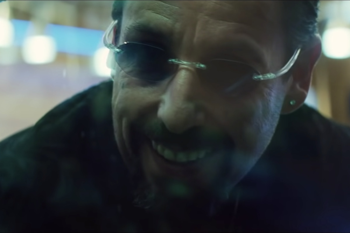 """Still image from """"Uncut Gems"""" of Adam Sandler's character Howard Ratner grinning through a window."""