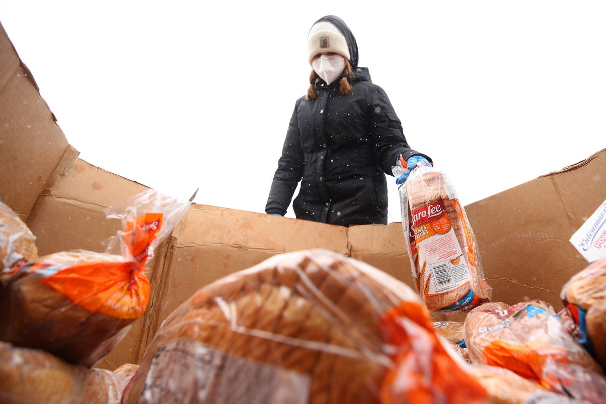 OAK PARK, MICHIGAN - APRIL 15: Keely O'Keefe of Birmingham and a Forgotten Harvest volunteer prepares to load bread into a car on April 15, 2020 in Oak Park, Michigan. The organization distributes food throughout the metro area, which has seen an uptick in demand due to the COVID-19 pandemic.