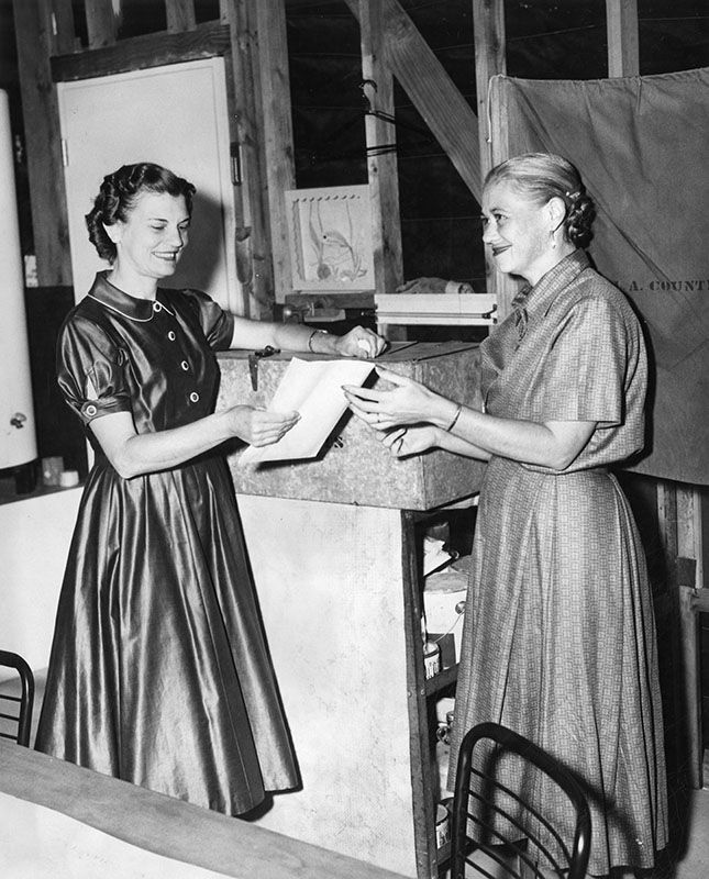 """Photograph caption dated June 3, 1958 reads: """"Mrs. Michael McGarvey, right, casts first vote in Burbank Precinct 125 at 531 N. Frederick St. as statewide primary election begins. Accepting ballot is precinct official Mrs. Fred Brammer."""""""