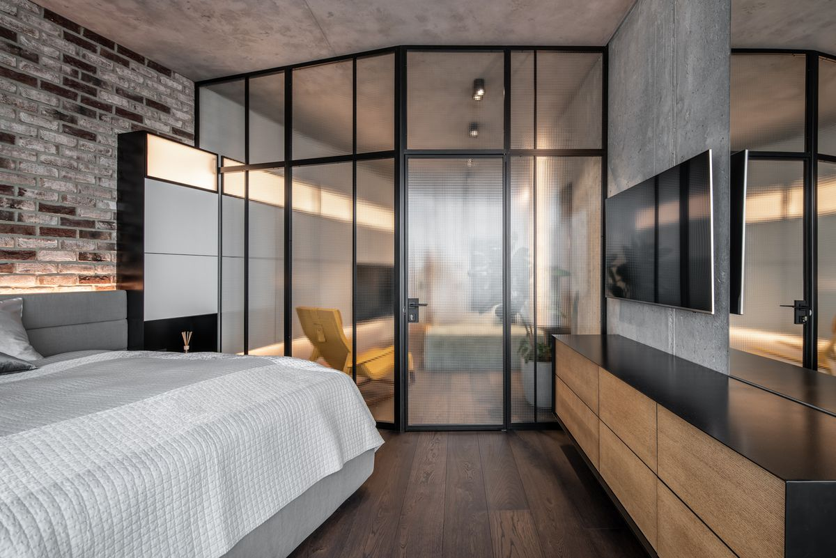 Bedroom separated from living room by opaque glass wall.