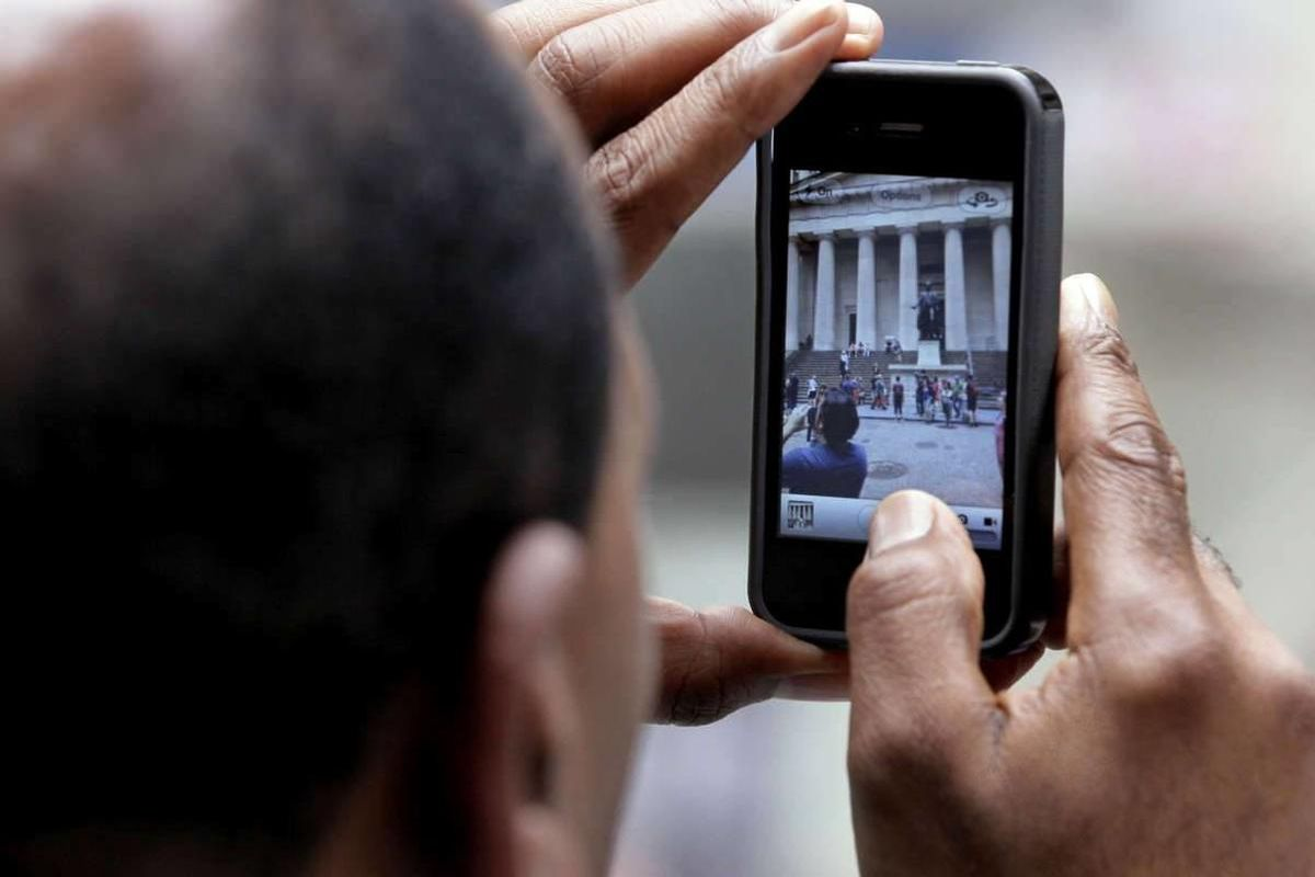 FILE - In this Wednesday, May 30, 2012, file photo, a tourist uses his iPhone to photograph Federal Hall in New York's Financial District, May 30, 2012. Leap Wireless International Inc., the parent of the Cricket cellphone service, on Thursday, May 31, 20
