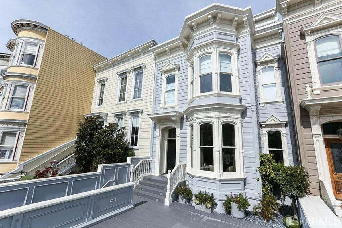 Baby blue exterior shot of tow-floor Victorian house.