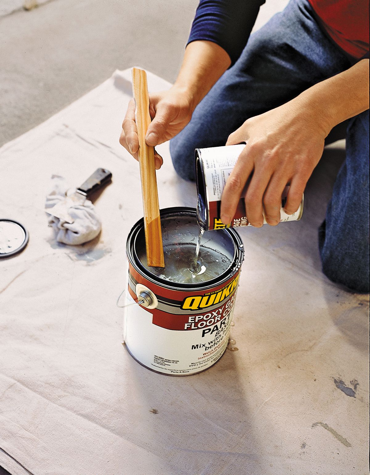 Person mixing epoxy paint with hardener in a paint can.