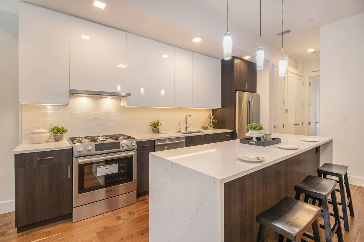 A kitchen with white countertops and stainless steel appliances. Black stools are at one end of the island.