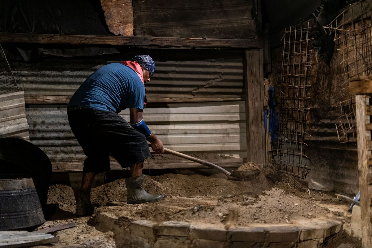 A master barbacoa cook piles dirt on a hole covered with goat.
