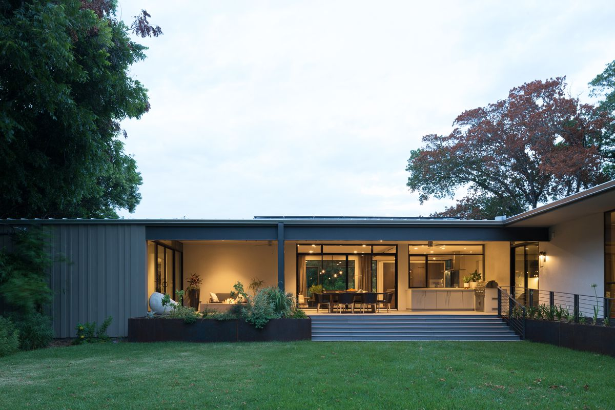 long, low flat-roofed contemporary with modernist influences, gray, lighted from inside, a few stairs to porch, lawn
