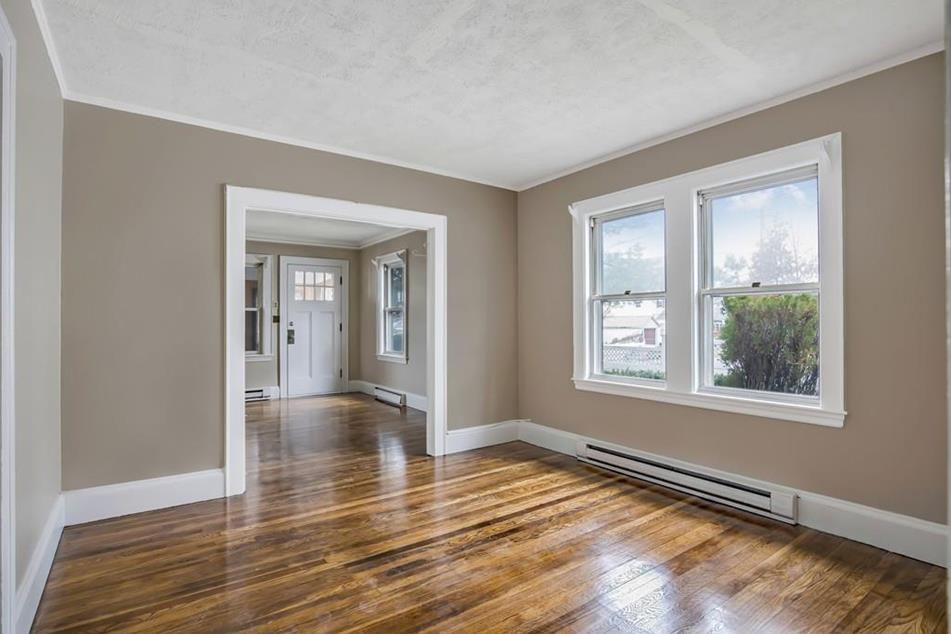 An empty room with a wide entryway and two large windows.