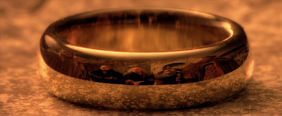 Image: Gimli, Legolas, and other characters arguing at the Council of Elrond, reflected on the surface of the One Ring in The Fellowship of the Ring.