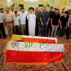 Mourners pray in front of the Iraqi flag-draped coffins of bomb victims, Talib Hassan, 35, and Hamza Jabbar, 37, during their funeral processions at the holy shrine of Imam Ali in Najaf, 100 miles (160 kilometers) south of Baghdad, Iraq, Sunday, July 3, 2016. Dozens of people have been killed and more than 100 wounded in two separate bomb attacks in the Iraqi capital Sunday morning, Iraqi officials said.
