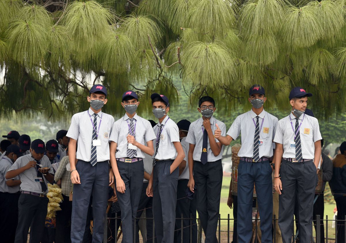 School students cover their faces with anti pollution masks during light rainfall, on November 7, 2019 in New Delhi, India