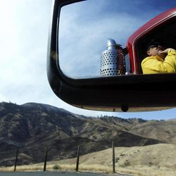 Firefighter Rob White, of the Arlington Heights, Wash., fire dept., is reflected in the mirror of his truck as he keeps an eye on one edge of a wildfire burning near Wenatchee, Wash. Crews in central Washington and Wyoming worked Monday to protect homes from two of the many wildfires burning throughout the West as a destructive fire season stretches into September with no relief expected from the weather anytime soon. The National Weather service issued red-flag warnings for wide swaths of eastern Washington and Oregon, Idaho, Montana and all of Wyoming, meaning conditions could exacerbate blazes.