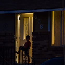 A boy across the street watches a candlelight vigil for the victims of a triple homicide at 639 N. Sir Philip Drive in Salt Lake City on Saturday, Sept. 19, 2015.