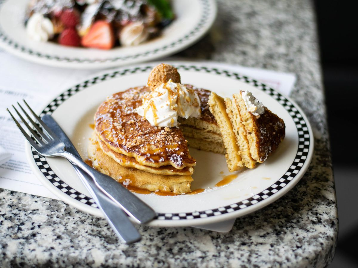 A stack of pancakes sits on a white plate with a black and white checkered border on the edge of a marble table.