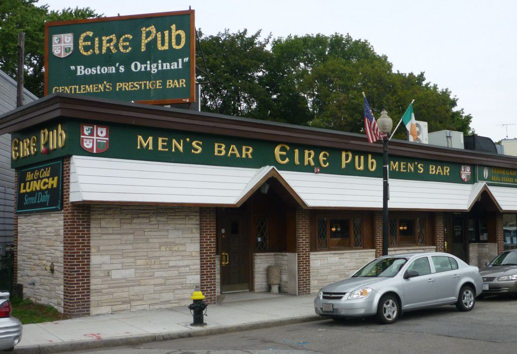 """Exterior of an old pub with light brick and green trim, with gold font reading """"Men's Bar Eire Pub"""""""