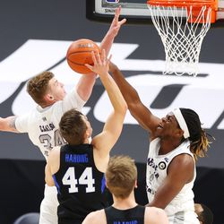 Brigham Young Cougars guard Connor Harding (44) is blocked by Weber State Wildcats center Dontay Bassett (21) as BYU and Weber State play an NCAA basketball game at Vivint Smart Home Arena in Salt Lake City on Wednesday, Dec. 23, 2020.