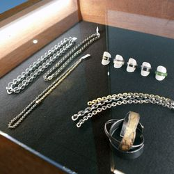 Men's jewelry, including jadite rings and sterling silver chain necklaces.