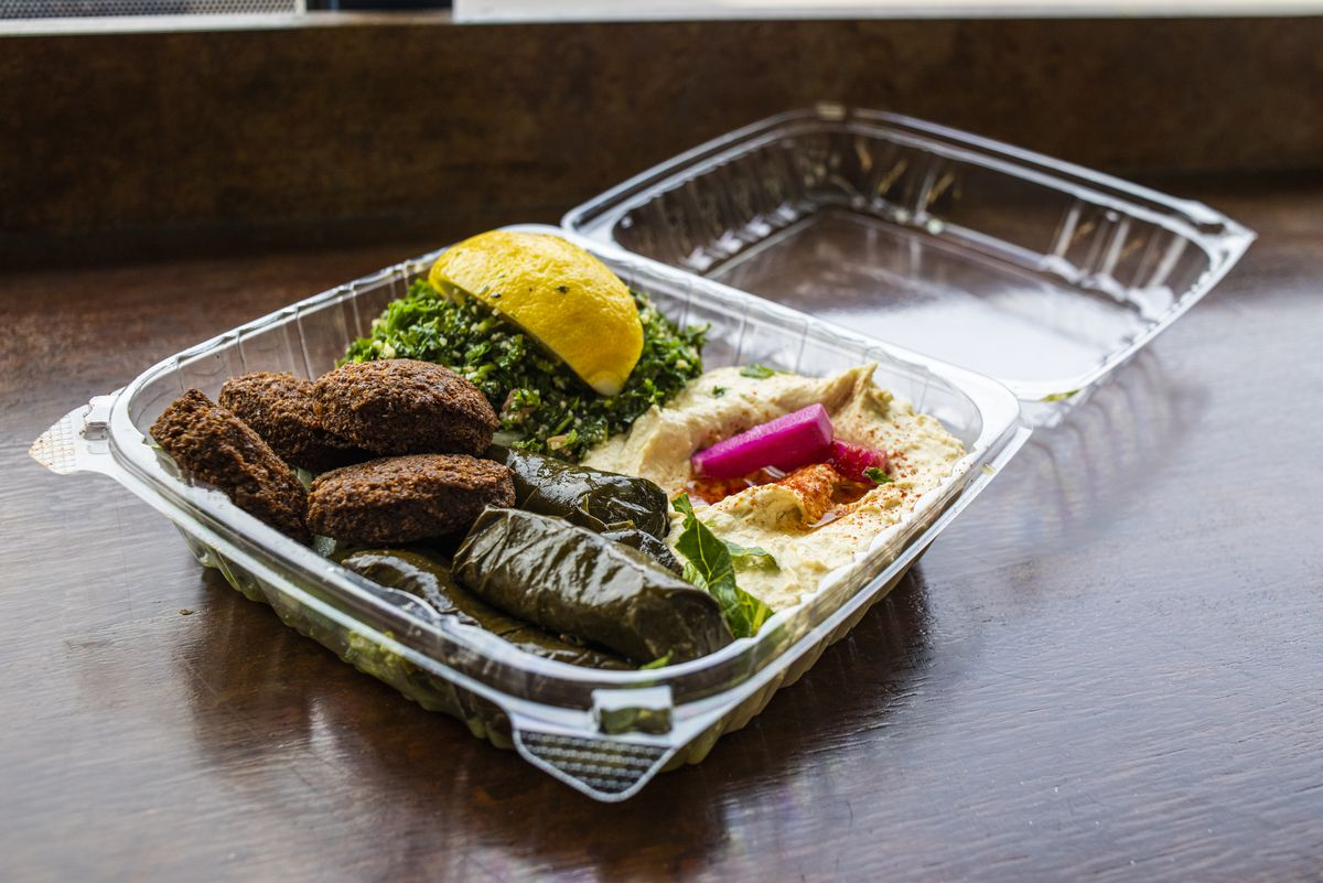 A plastic takeout container filled with stuffed grape leaves, hummus, falafel, and tabbouleh.