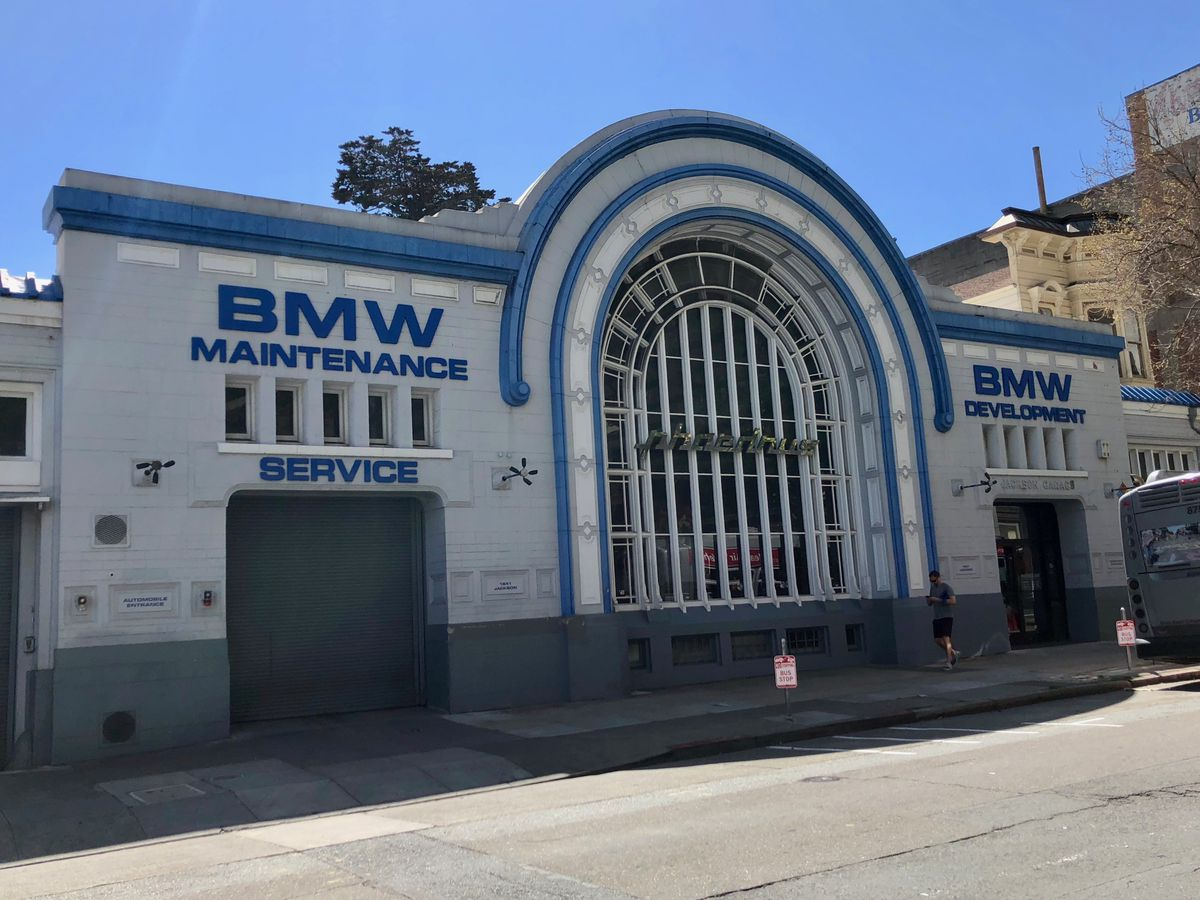 The exterior of 1641 Jackson in San Francisco. The facade is white with an arched entrance. There is a sign on the building that says: BMW Maintenance.