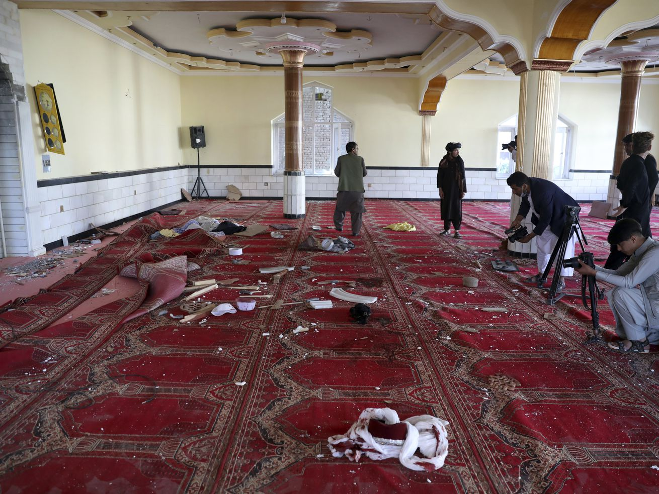 Afghan journalist take photos and film inside a mosque after a bomb explosion in Shakar Dara district of Kabul, Afghanistan, Friday, May 14, 2021. A bomb ripped through a mosque in northern Kabul during Friday prayers killing 12 worshippers, Afghan police said.