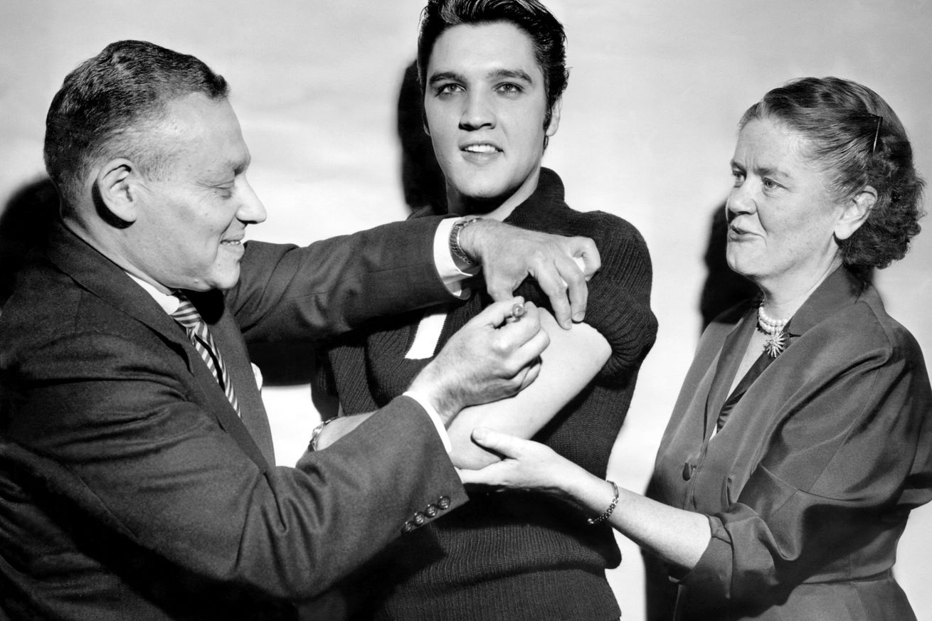 Elvis Presley receiving a polio vaccination from Dr. Leona B