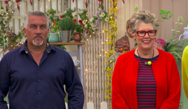 A smiling Prue Leith, wearing a red blazer, striped shirt, and a necklace on a black cord with a yellow and gray ball, standing next to a frowning Paul Hollywood.