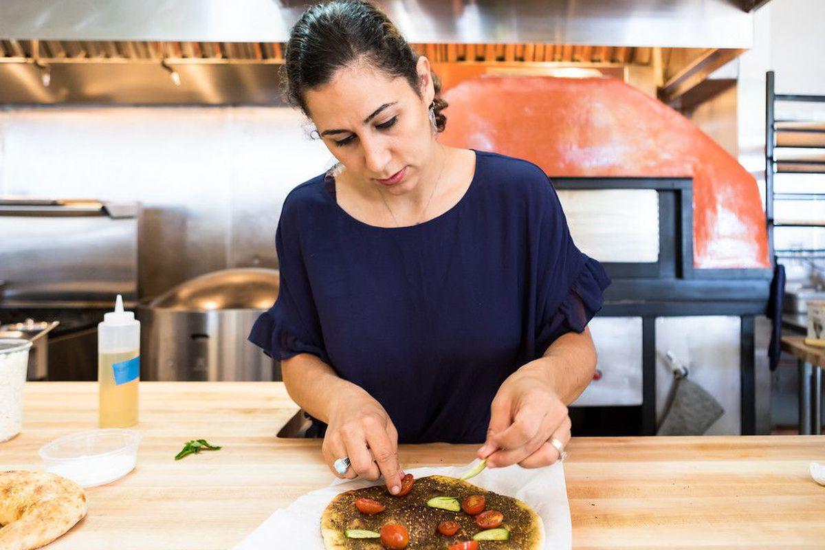 Reem Assil prepares a flatbread at bakery Reem's California
