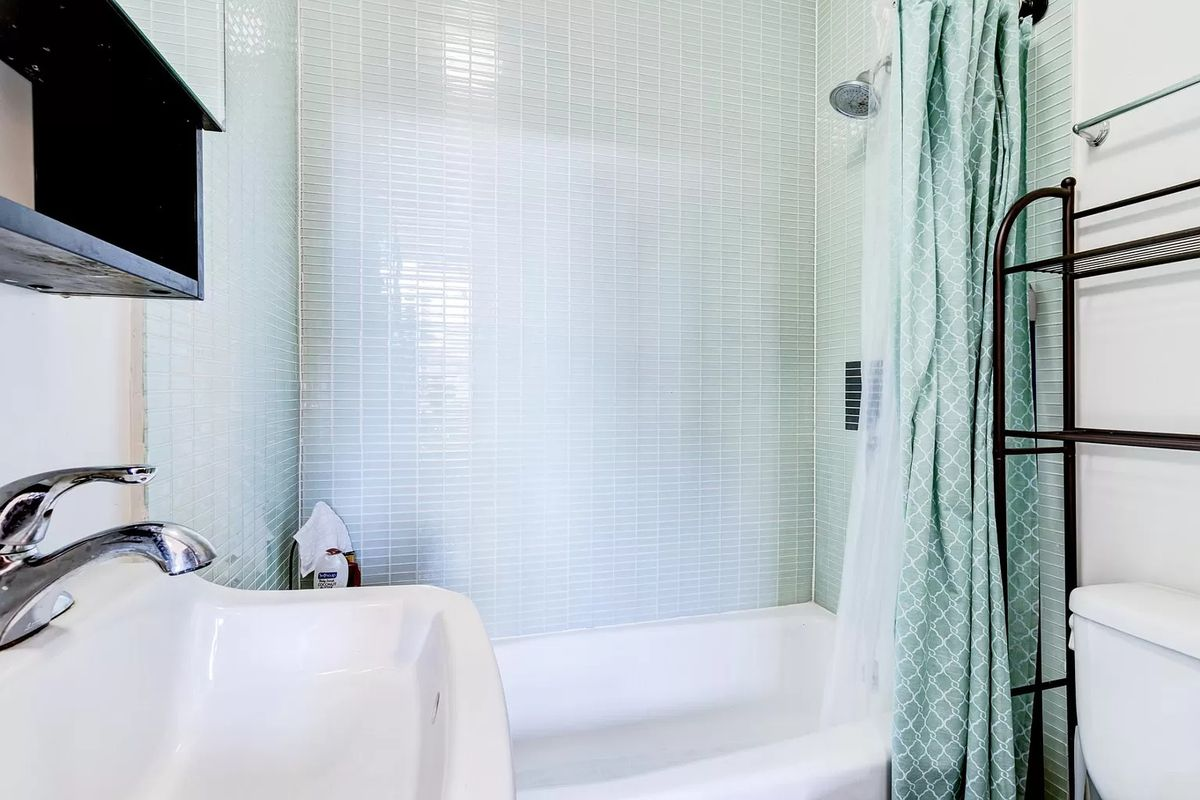 Bathroom with light green tiles, and a sink on the left.