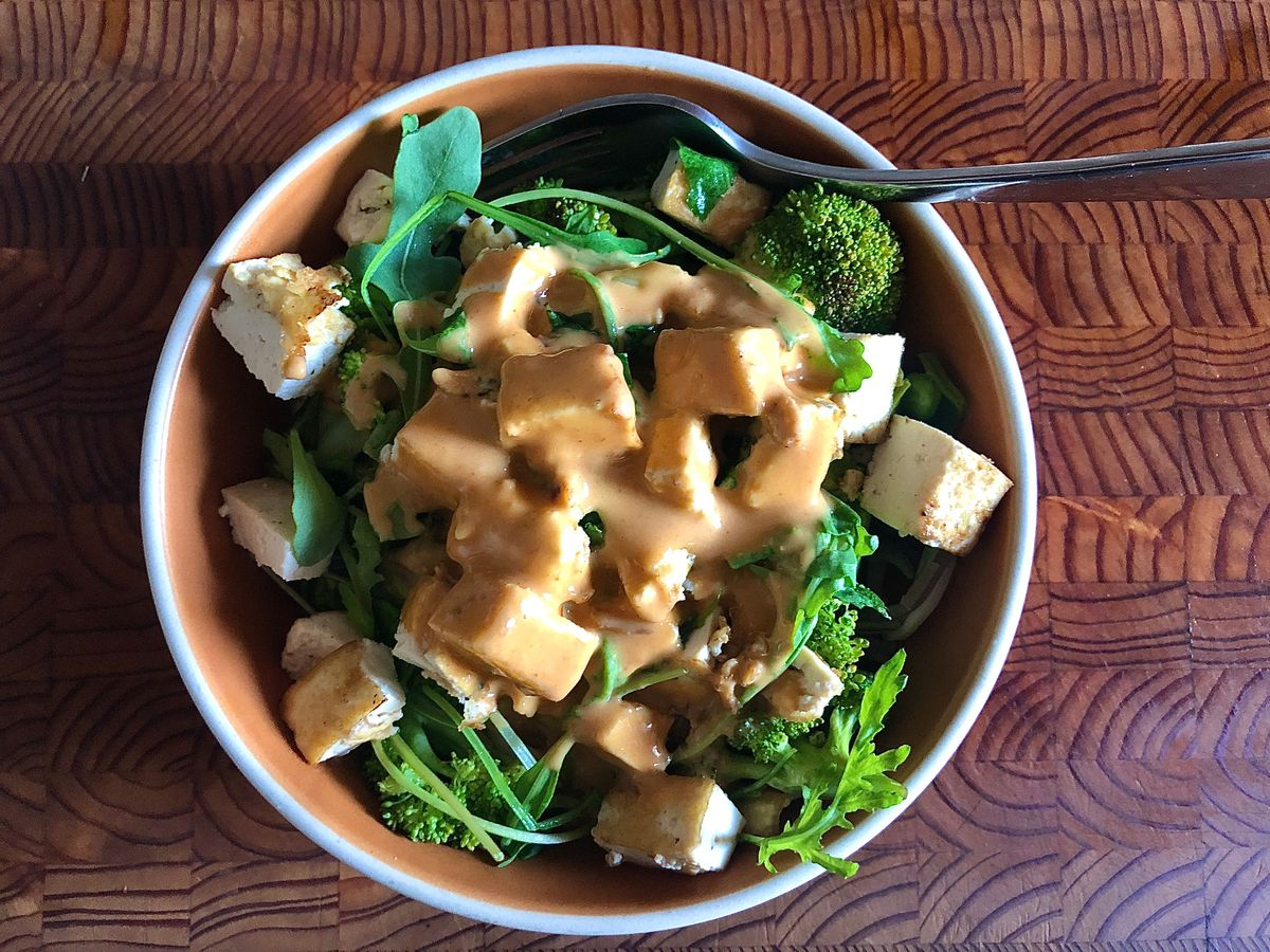 A white-rimmed orange bowl piled with arugula, tofu, broccoli, soba noodles, and peanut sauce sits on a wooden cutting board.