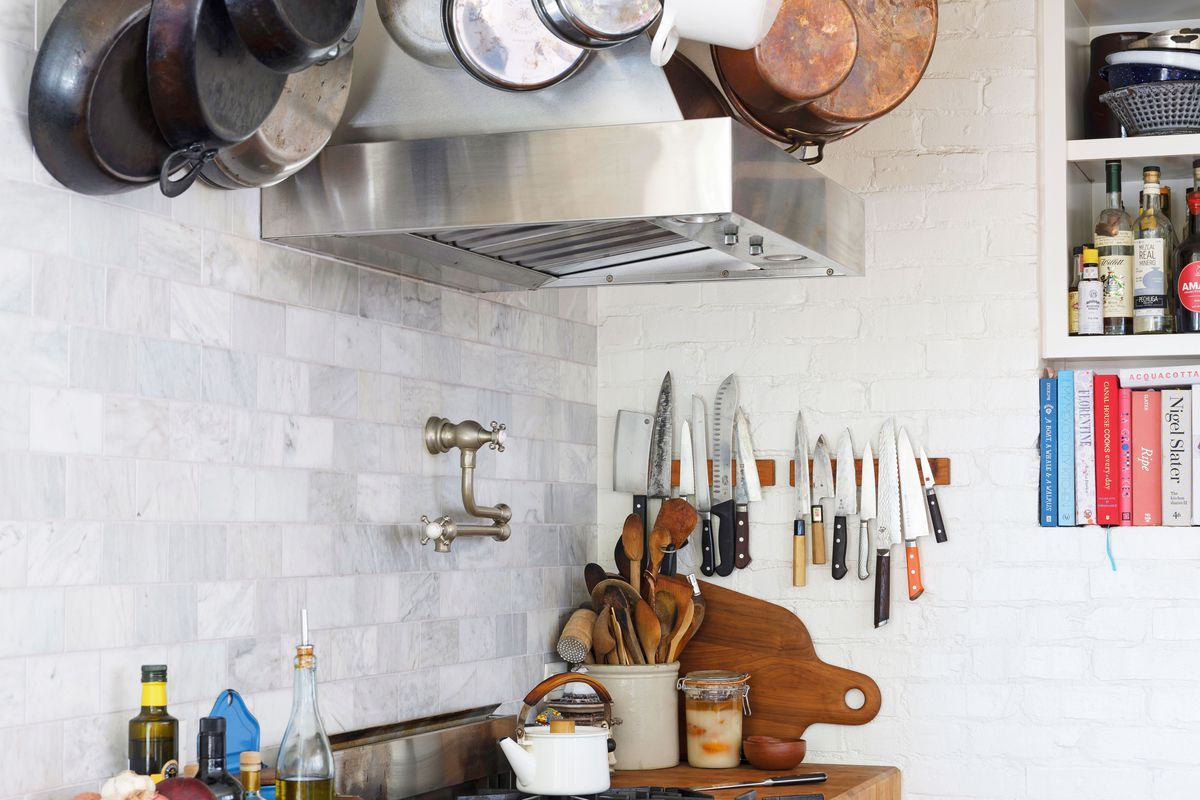 A kitchen area with a stove and wooden countertops. There is a rack with hanging pots and pans. On the wall are magnetized wood blocks that are holding multiple knives. There are built-in shelves with books, bottles, and kitchen wares.