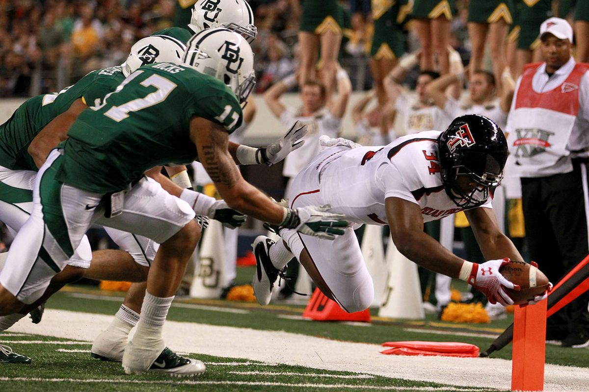 ARLINGTON, TX - NOVEMBER 26:  Kenny Williams #34 of the Texas Tech Red Raiders dives for a touchdown against Mike Hicks #17 of the Baylor Bears at Cowboys Stadium on November 26, 2011 in Arlington, Texas.  (Photo by Ronald Martinez/Getty Images)