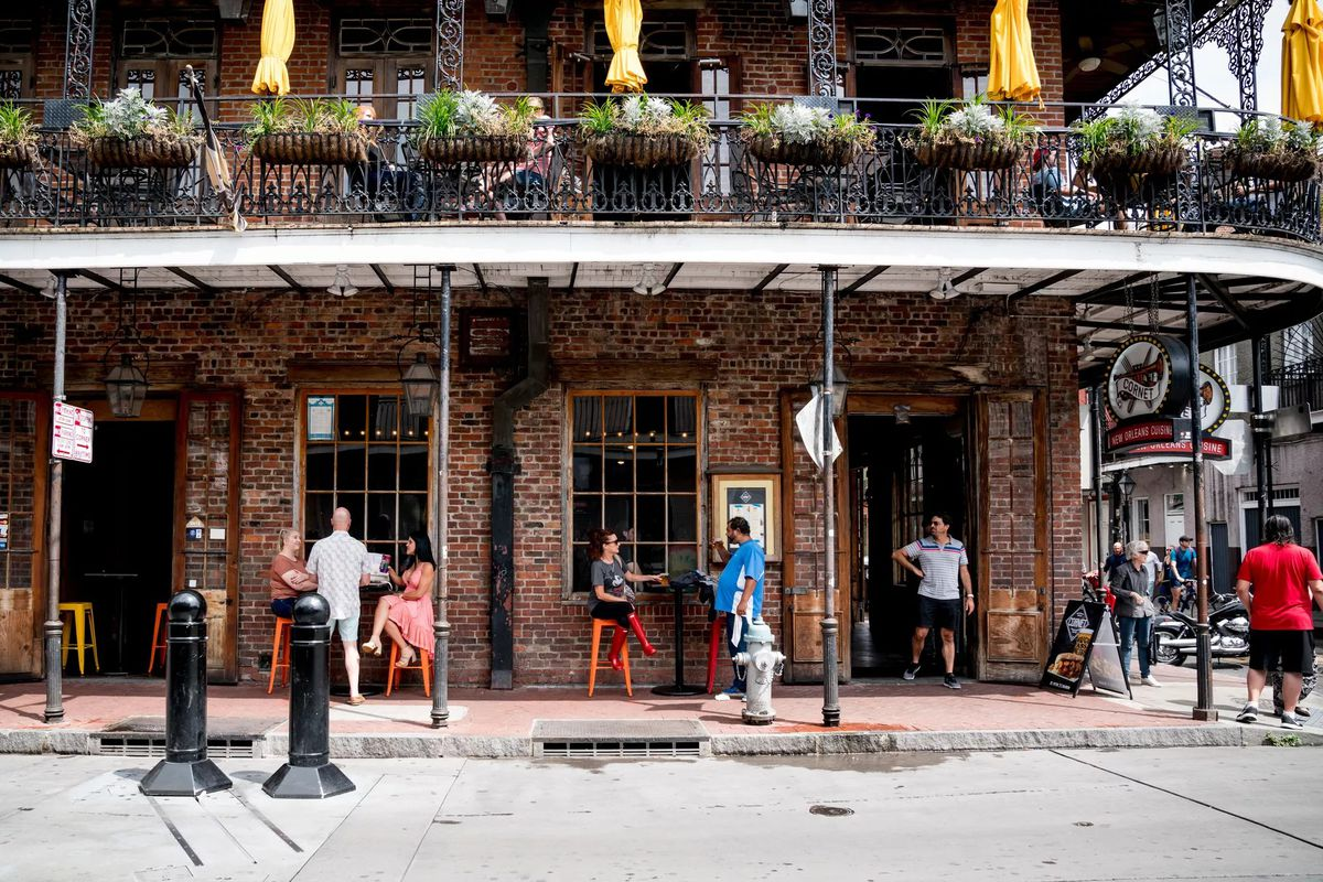 Customers sit at tables on a sidewalk outside of a corner bar in New Orleans's French Quarter