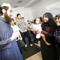 Imam Muhammed Shoayb Mehtar talks to Sumeya Abdalla, holding Liyazia Mohamed, and Salma Abdalla at the Khadeeja Islamic Center in West Valley City, Utah.