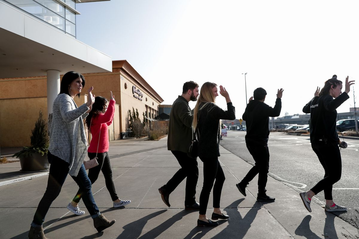 Shoppers evacuate with their hands in the air after a shooting at Fashion Place Mall in Murray on Sunday, Jan. 13, 2019.