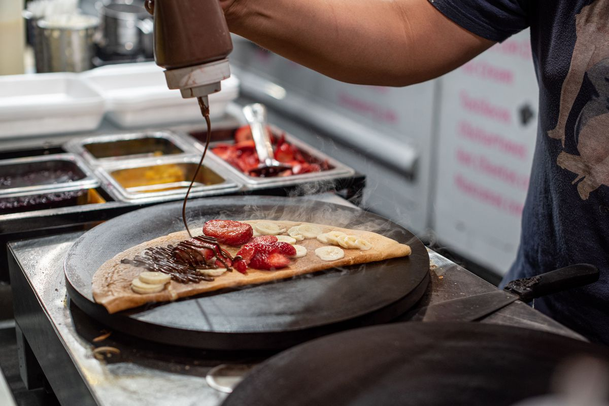 Preparing a crepe with chocolate and banana and strawberries at a night market.