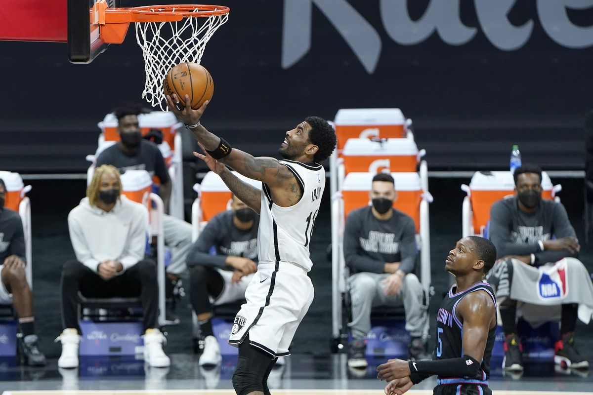 Kyrie Irving of the Brooklyn Nets goes in for a fast break layup in front of De'Aaron Fox of the Sacramento Kings during the first half of an NBA basketball game at Golden 1 Center on February 15, 2021 in Sacramento, California.