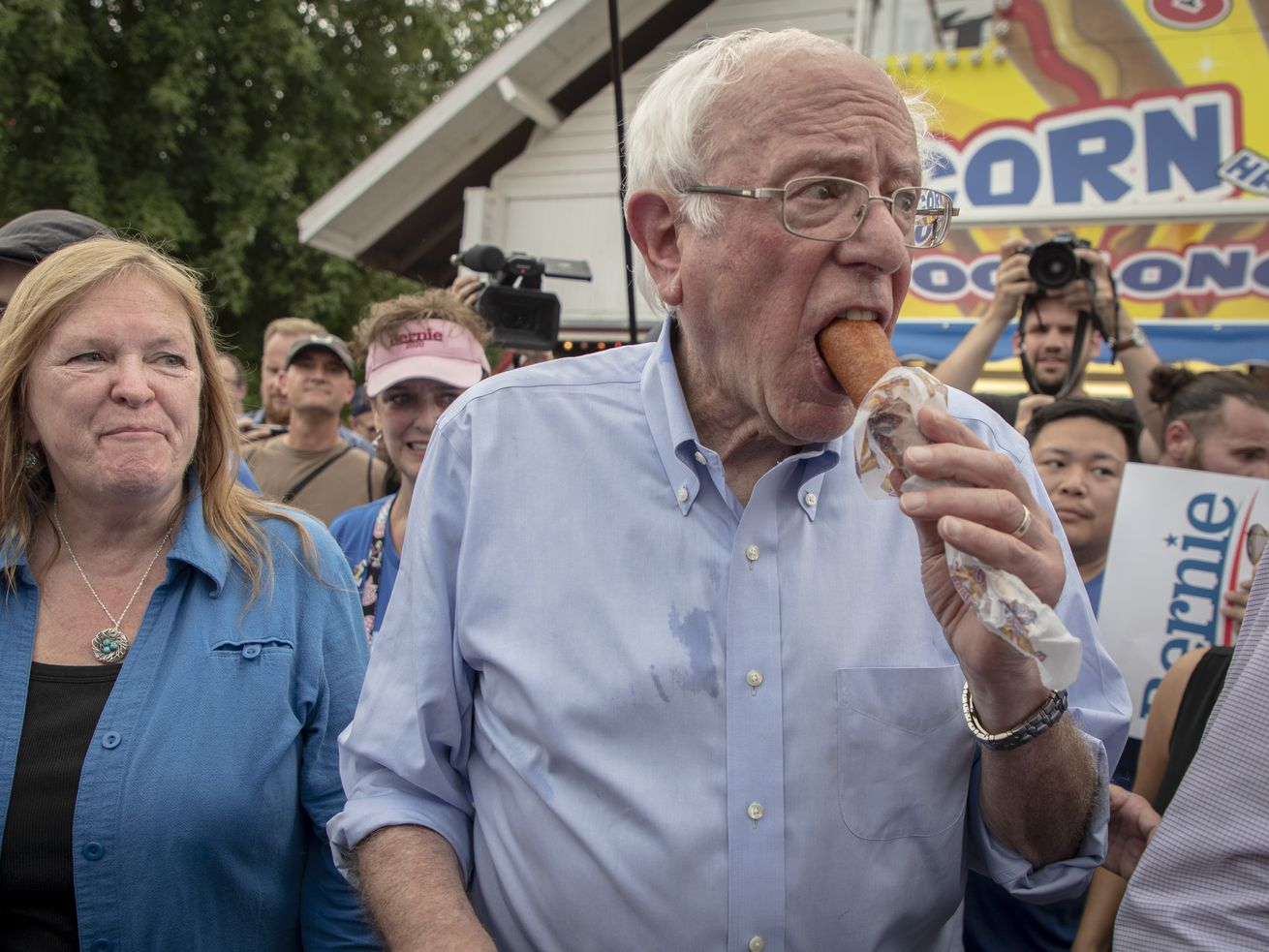 Sanders walks while eating a corn dog, with supporters following behind him.