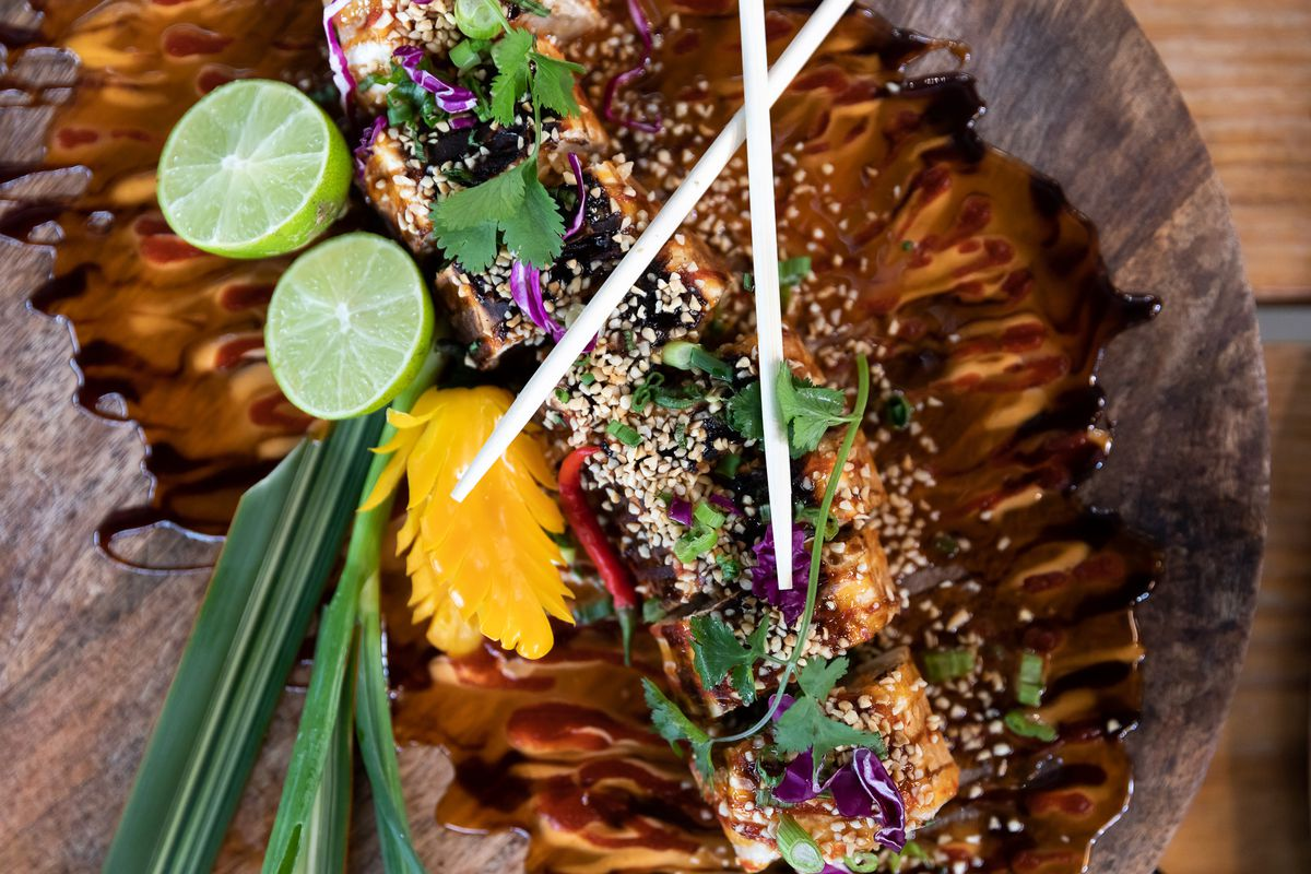 A sliced pad thai roll surrounded by herbs, sliced lime, chopsticks, and a pool of brown sauce.