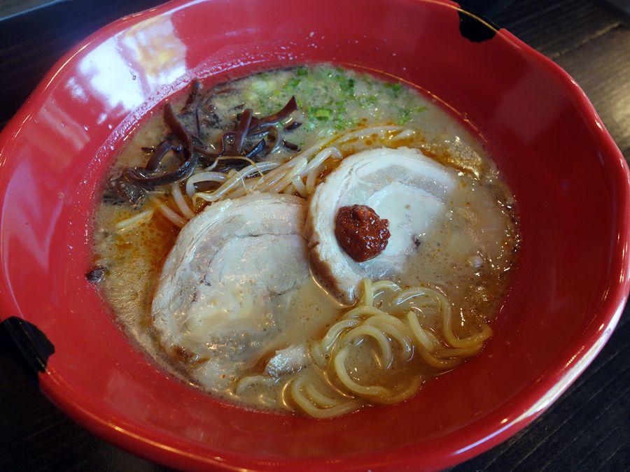 A red bowl of tonkotsu spicy ramen with pork.