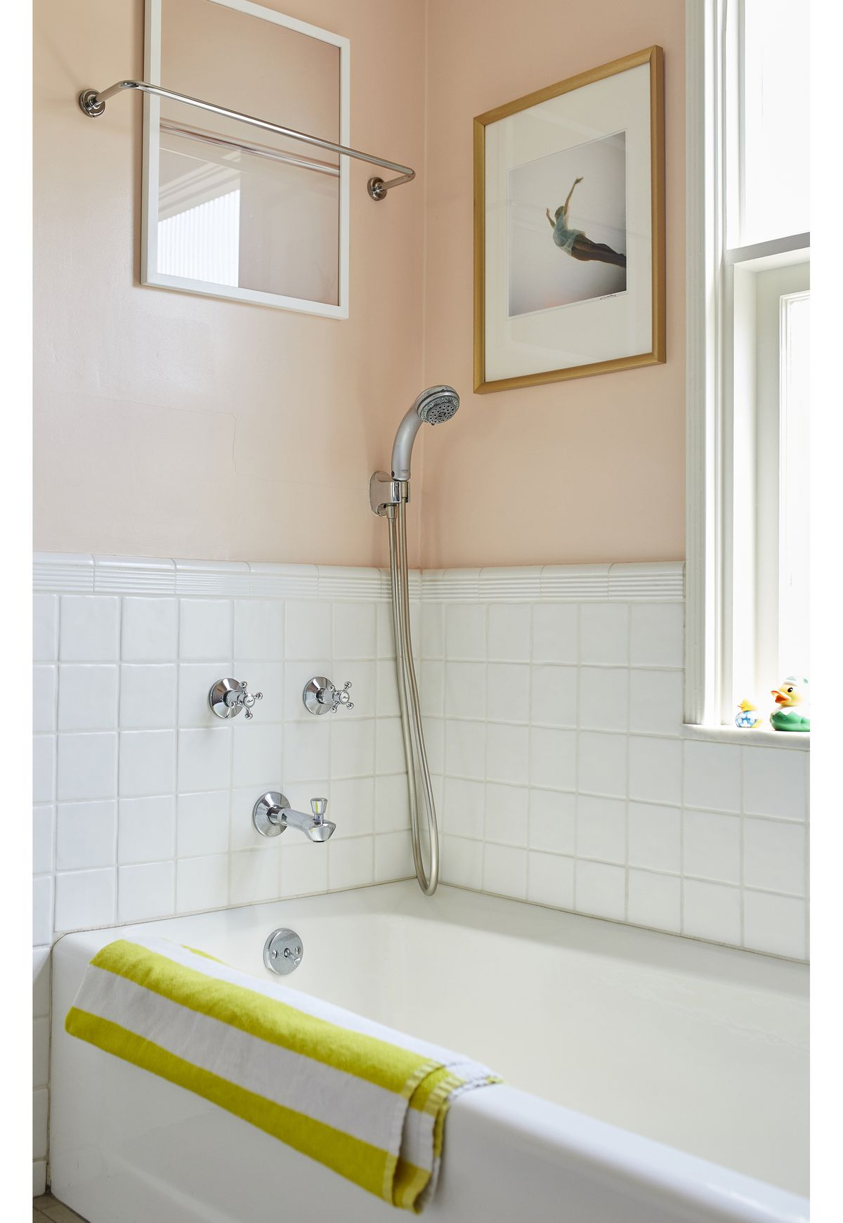 A bathroom with white tiles, a white bathtub and peach walls. There are two framed photographs hanging above the tub.