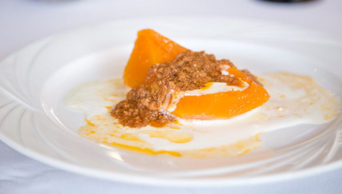 Baked pumpkin on yogurt, topped with a ground beef sauce, on a white plate
