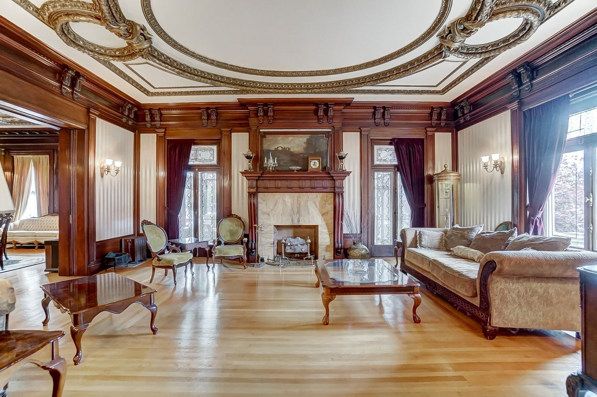 A living room has a large formal couch, several coffee tables and arm chairs, woodworking, wood floors, and crown molding.