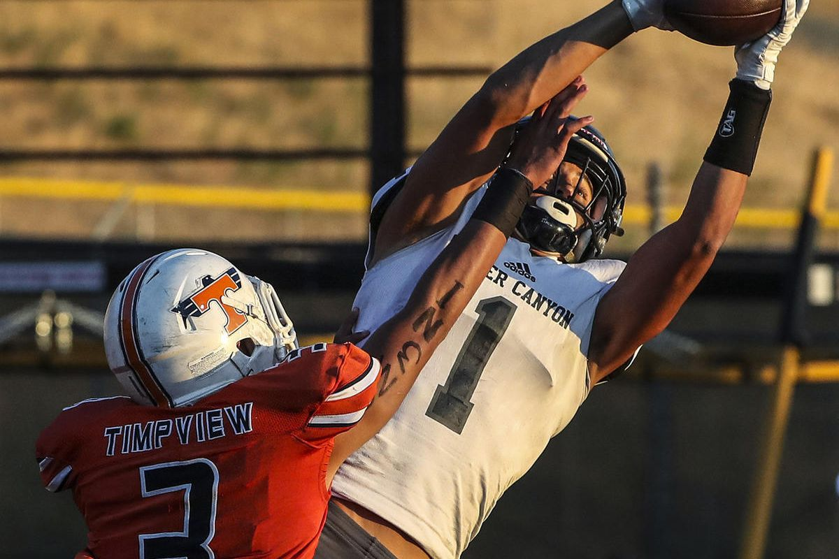 Corner Canyon wide receiver John Mitchell makes a leaping touchdown catch over Timpview cornerback Raider Damuni during game at Timpview in Provo on Friday, Sept. 21, 2018.