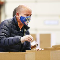 Gov.-elect Spencer Cox smiles at a worker through his mask as he, his wife, Abby, and members of their family volunteer at the Utah Food Bank in St. George on Saturday, Jan. 2, 2021.