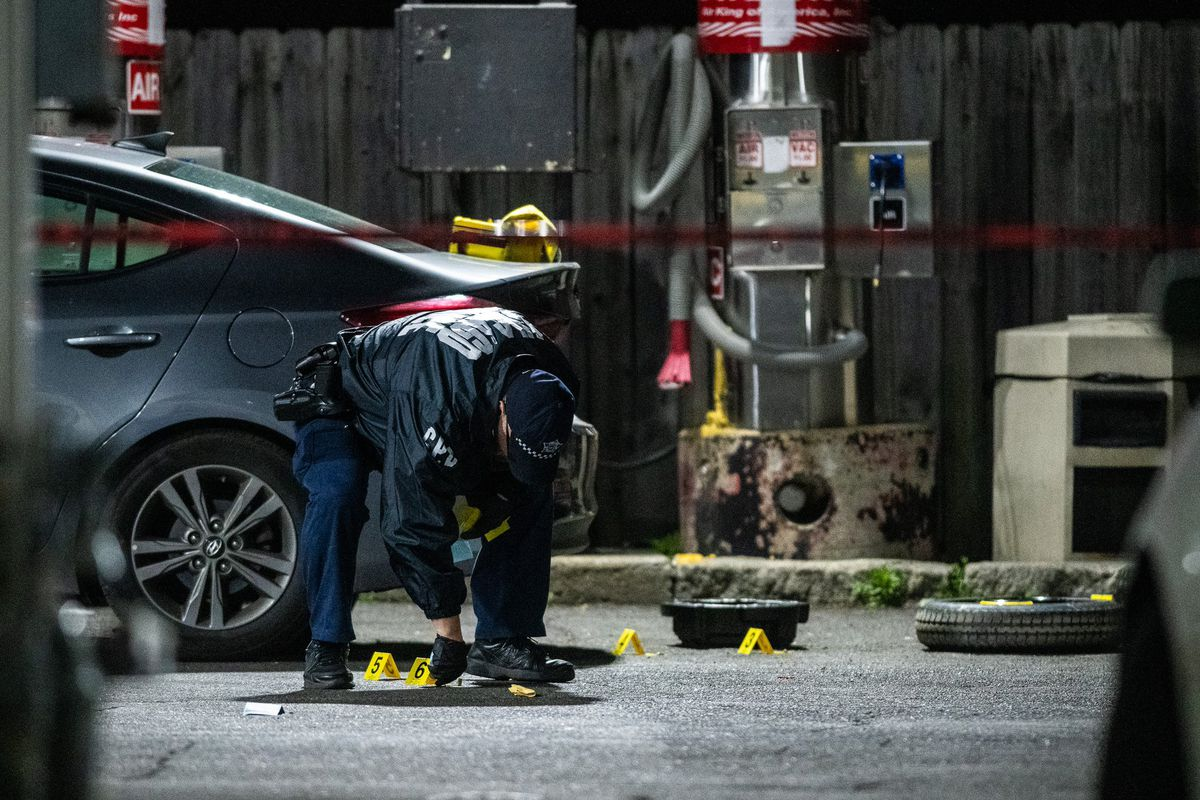 A police officer bends over evidence markers near a car where two women were shot