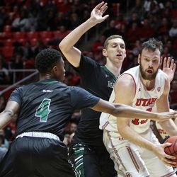 Utah Utes forward David Collette (13) takes one more dribble before taking a shot over Hawaii Warriors guard Brandon Thomas (4) and center Ido Flaisher (15) as Utah hosts Hawaii at the Huntsman Center in Salt Lake on Saturday, Dec. 2, 2017.