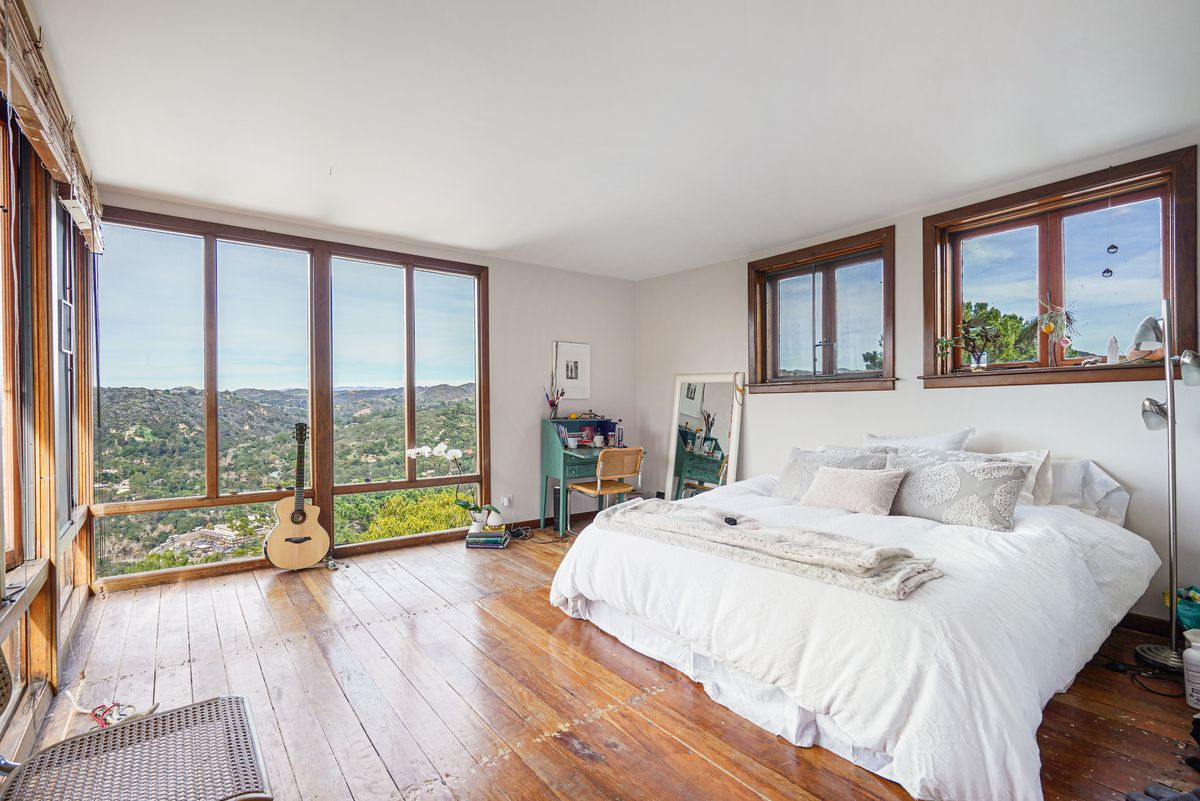 A room furnished with a bed; it has wood floors and floor-to-ceiling windows on the left wall
